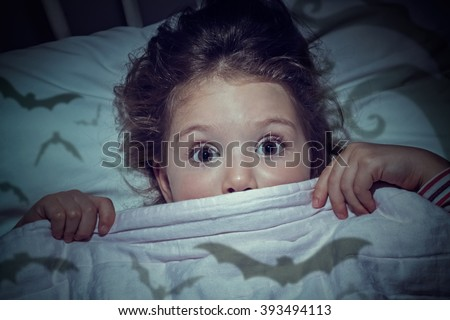 scared cute little girl under the blanket in her bed. Imagination of children concept. - stock photo