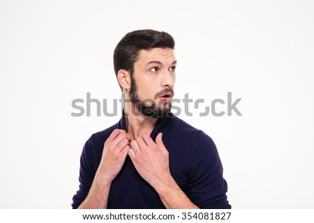 Scared dazed handsome young man with beard in sweetshirt looking away over white background - stock photo