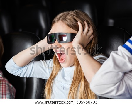 Scared girl screaming while watching 3D movie in cinema theater - stock photo