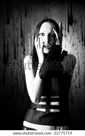 Scared goth woman portrait. Background with dirty spots. - stock photo