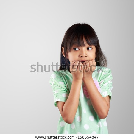 Scared little girl hiding face on grey background with clipping path - stock photo