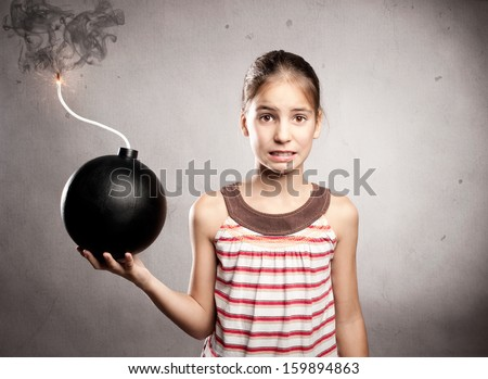 scared little girl holding an old fashioned bomb - stock photo