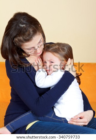 Scared little girl hugging her mother - stock photo