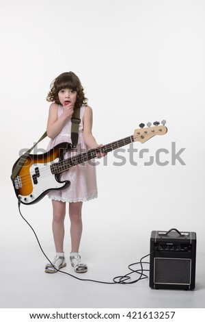 Scared little princess with huge for her bass guitar. Opened mouth and big eyes. Small special amp in the corner. Small child made a mistake while playing the instrument. Isolated. - stock photo