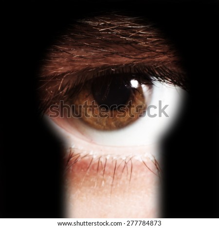Scared male eye spying through a keyhole - stock photo