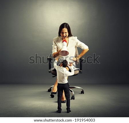 scared man and angry woman over dark background - stock photo