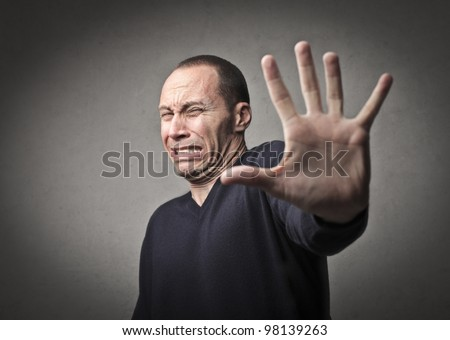 Scared man indicating to halt with his hand - stock photo
