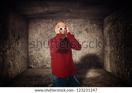 Scared man with anaglyph glasses screaming  while watching a 3d movie. - stock photo