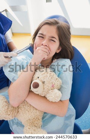 Scared patient covering mouth and holding teddy bear in dental clinic - stock photo