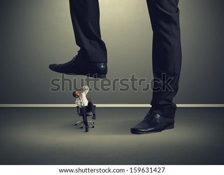 scared small man under big leg - stock photo