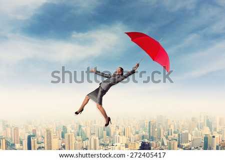 Scared woman flying in the sky with umbrella - stock photo