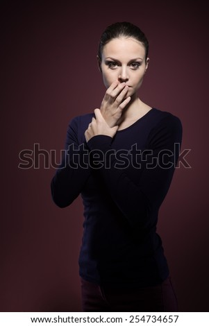 Scared woman staring at camera on dark background - stock photo
