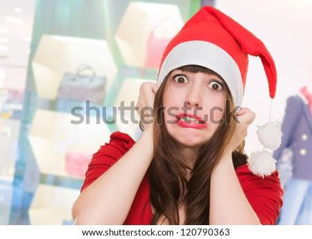 scared woman wearing a christmas hat in front of a shop - stock photo