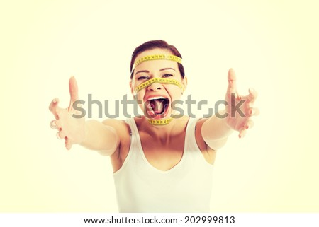Scared woman with measuring tape on face - stock photo