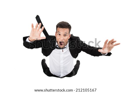 Scared young businessman in falling position. flying businessman on white background and crying - stock photo