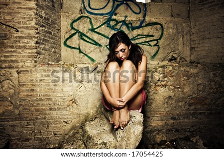 Scared young girl in a dirty place, corrupted makeup. - stock photo