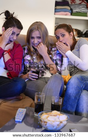 Scared young girls watching horror movie on television - stock photo