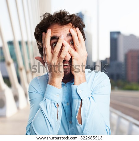 scared young man covering face - stock photo