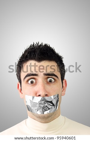Scared young man having gray duct tape on his mouth.Gradient background with copy space. - stock photo
