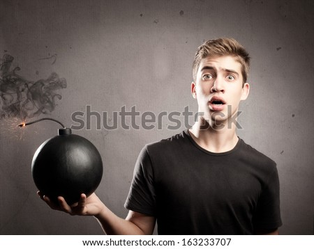 scared young man holding an old fashioned bomb - stock photo