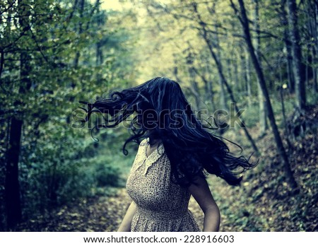 Scared young woman running through a forest at night, looking back - stock photo