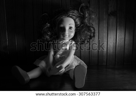 Scary black and white photo of a girl doll side lit and heavy shadows to create atmosphere with a wooden background. - stock photo