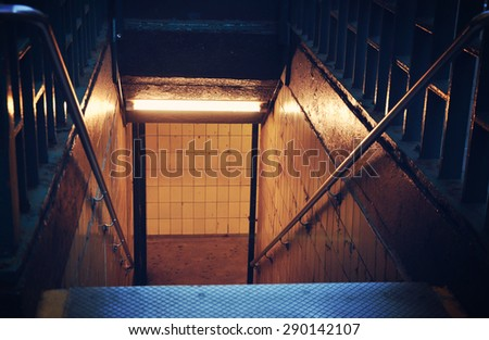 Scary city stairs are leading down to a subway station for a danger or fear concept. - stock photo