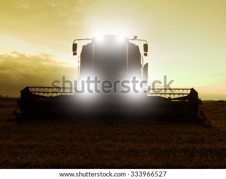Scary combine harvest wheat in the middle of a farm field. Morning yellow wheat field on the sunset cloudy orange sky background. - stock photo