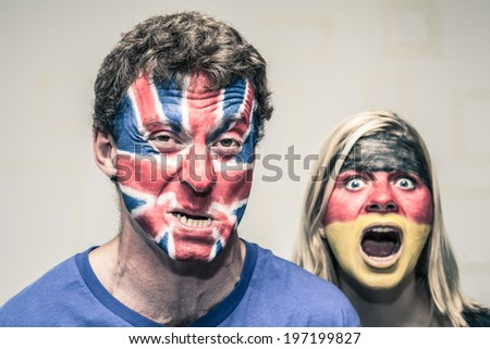 Scary couple with painted British and German flags on faces. - stock photo