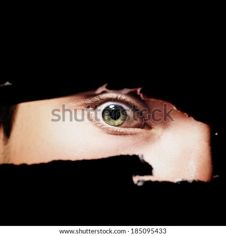 Scary eye of a man spying through a hole in the wall closeup - stock photo
