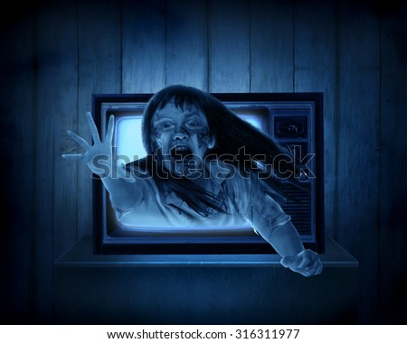 Scary ghost out from old television. Halloween concept - stock photo