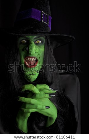 Scary green witch, Low key lighting. - stock photo