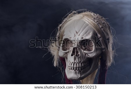 Scary grim reaper halloween skull on a smoky background - stock photo