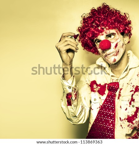 Scary Grunge Clown In Dirty Business Suit And Tie Drawing On The Walls With A Red Pen For You To Write Your Halloween Message In Blood - stock photo