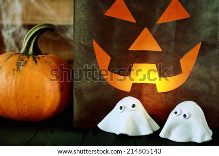 Scary Halloween party background with a glowing paper bag jack-o-lantern with a fiendish face alongside a fresh pumpkin and cute scary little ghosts made of pastry dough for a creative snack - stock photo