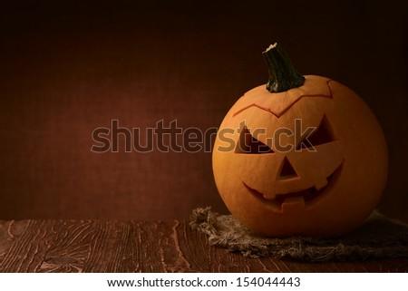Scary halloween pumpkin jack-o-lantern on dark background - stock photo