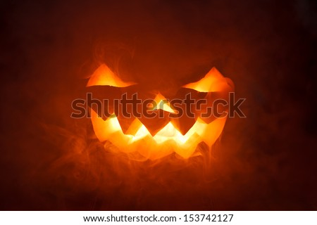 Scary Halloween Pumpkin looking through the smoke. Glowing, smoking monster pumpkin from depths of hell - stock photo