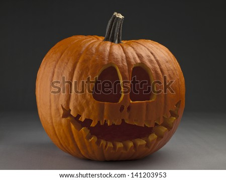 Scary Halloween pumpkin lying on a gray background - stock photo