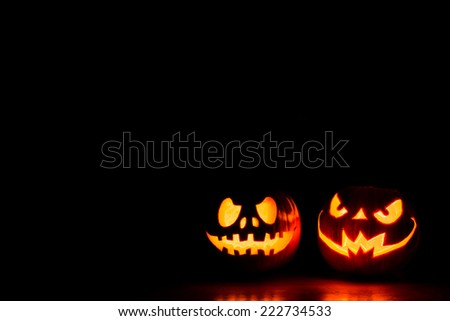 Scary Halloween pumpkins on a black background with space for text. Halloween card concept. Spooky glowing faces - stock photo
