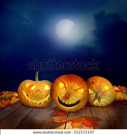 Scary halloween pumpkins on a wooden table - stock photo