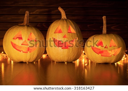 Scary Halloween pumpkins on wooden background - stock photo