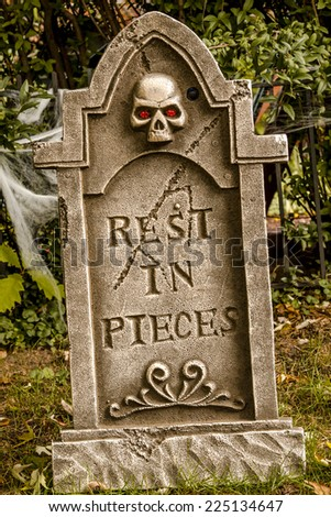 Scary Halloween skeleton gravestone  with rest in pieces message on front - stock photo