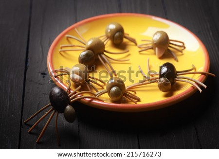 Scary Halloween spider appetizers made with cured black and green olives with spaghetti legs crawling over a yellow plate on a buffet against a dark background - stock photo