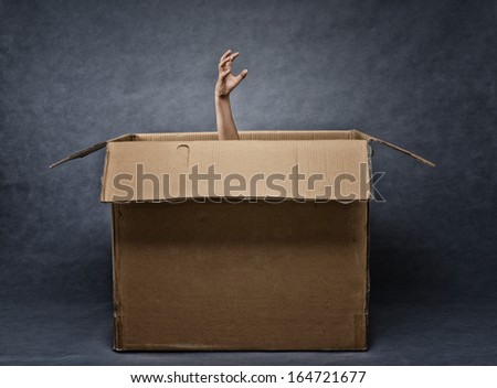 Scary hand coming out of box - stock photo