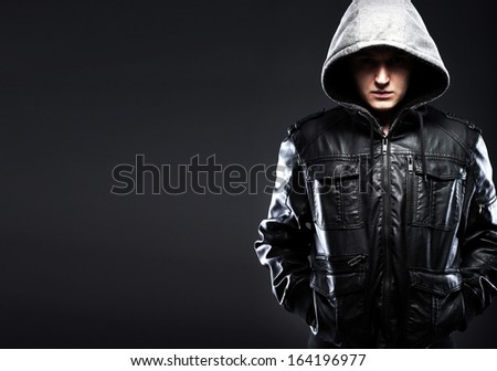 Scary hooligan man in leather jacket with a hood darkness background - stock photo