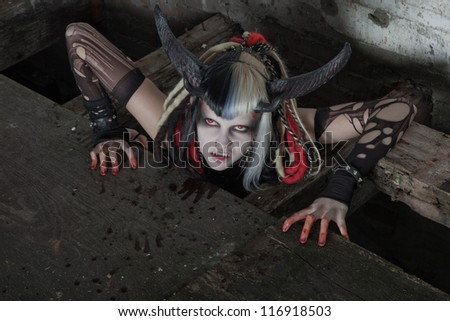 Scary hungry female demon crawling out of the floor. Bloody wall. - stock photo