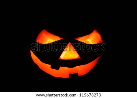 Scary Jack o' Lantern in the dark , illuminated from inside with bright orange eyes and mouth, specially created for Halloween night. - stock photo