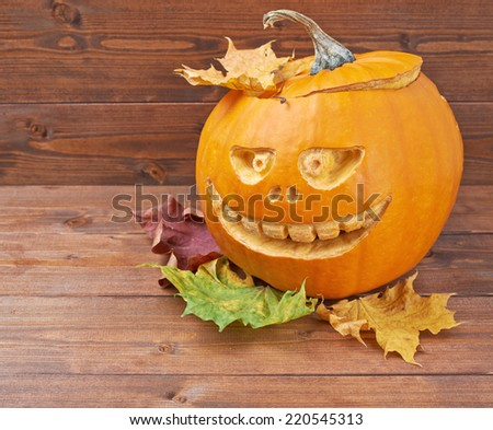 Scary jack o lantern pumpkin composition next to colorful maple leaves over the wooden boards surface - stock photo