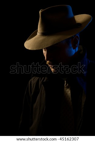 Scary-looking bad guy in hat, looking at you with menace - stock photo