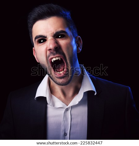Scary man in suit with black eyes and fangs screaming against black background. - stock photo